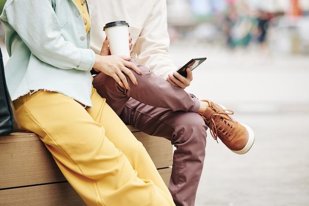 Bijgesneden afbeelding van jong stel dat koffie drinkt en nieuws op smartphone controleert wanneer ze buiten zitten
