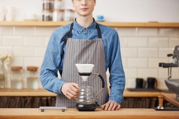 Bijgesneden afbeelding van jonge barista in uniform aan toog.