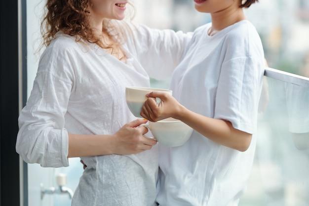 Bijgesneden afbeelding van jonge lesbische paar knuffelen en flirten tijdens het drinken van koffie in de ochtend op het balkon van het appartement