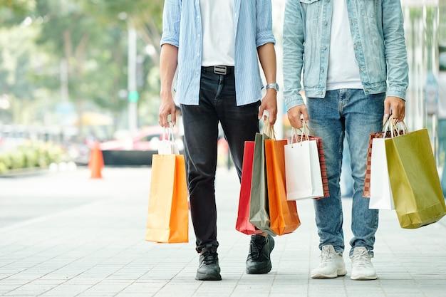 Bijgesneden afbeelding van jonge mannen die op straat lopen met veel boodschappentassen in handen
