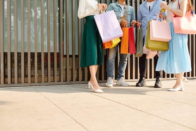 Bijgesneden afbeelding van jonge mensen met veel boodschappentassen buiten staan en aankopen bespreken
