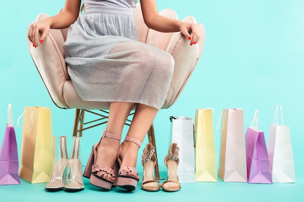 Bijgesneden afbeelding van jonge shopper vrouw 20s zittend op een stoel met veel sandalen en winkelpakketten, geïsoleerd over blauwe muur