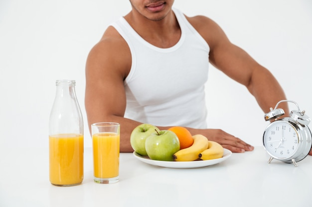 Bijgesneden afbeelding van jonge sportman in de buurt van fruit.