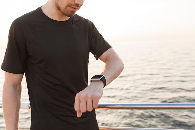 Bijgesneden afbeelding van jonge sportman in zwart t-shirt