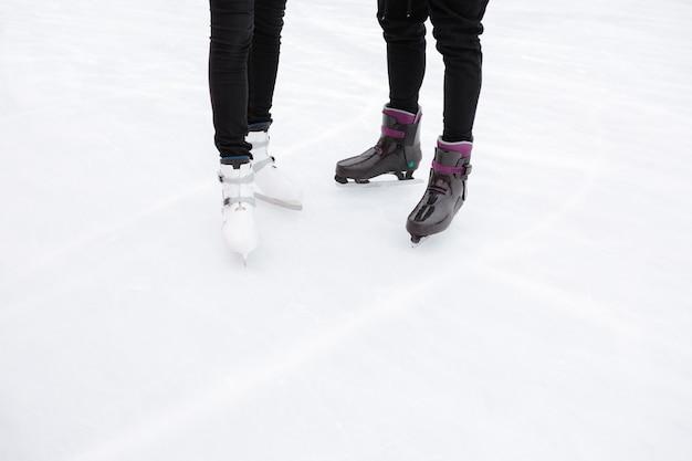Bijgesneden afbeelding van jonge verliefde paar schaatsen op de ijsbaan