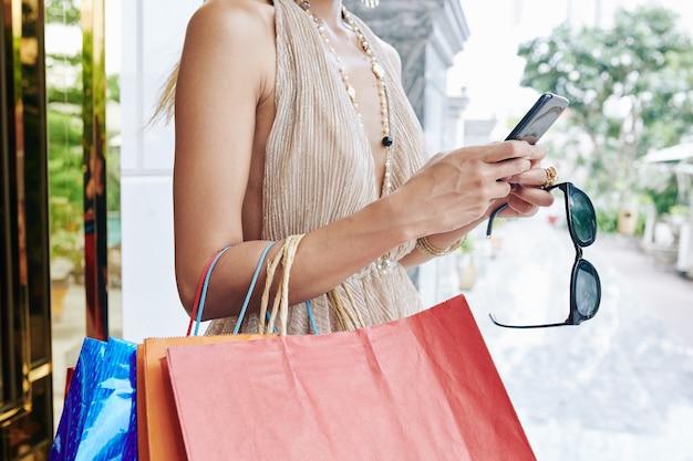 Bijgesneden afbeelding van jonge vrouw met zonnebril en boodschappentassen sms-berichten in haar smartphone controleren