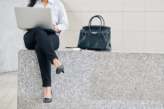 Bijgesneden afbeelding van jonge vrouwelijke ondernemer buiten zitten naast haar tas en werken op laptop