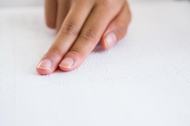 Bijgesneden afbeelding van kind hand braille boek lezen
