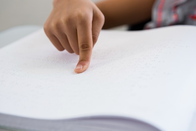 Bijgesneden afbeelding van kind lezen braille boek