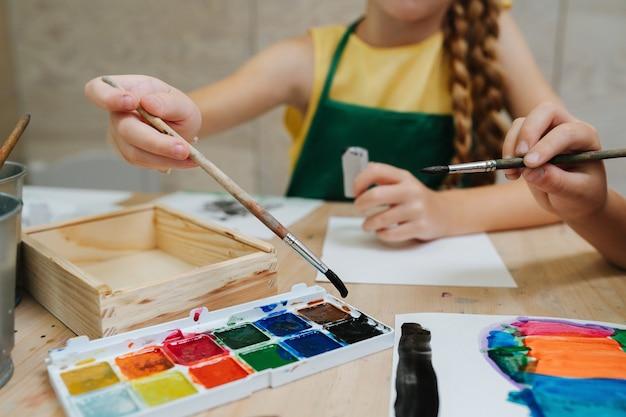 Bijgesneden afbeelding van kinderen schilderen met aquarel lage hoek