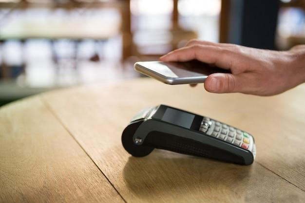 Bijgesneden afbeelding van klant hand betalen via slimme telefoon in coffeeshop
