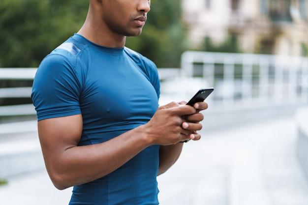 Bijgesneden afbeelding van knappe jonge sterke sportman buitenshuis met behulp van mobiele telefoon chatten.