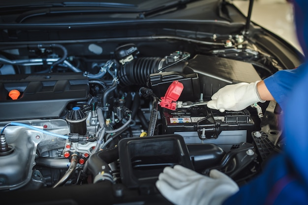 Bijgesneden afbeelding van knappe monteur in uniform werkt in auto service. autoreparatie en -onderhoud.