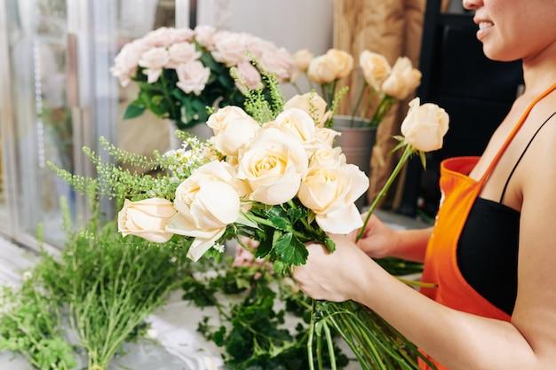 Bijgesneden afbeelding van lachende bloemist die een mooi boeket maakt met witte rozen en kamilles voor de bruid