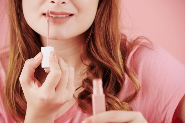 Bijgesneden afbeelding van lachende jonge vrouw oranje matte vloeibare lippenstift toe te passen