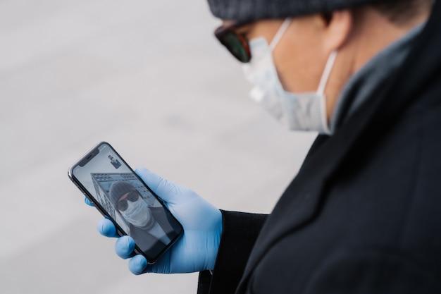 Bijgesneden afbeelding van man heeft videogesprek met beste vriend, houdt sociale afstand, is op zichzelf geïsoleerd tijdens het verspreiden van besmettelijk virus, draagt beschermend masker en handschoenen, houdt mobiele telefoon in de hand