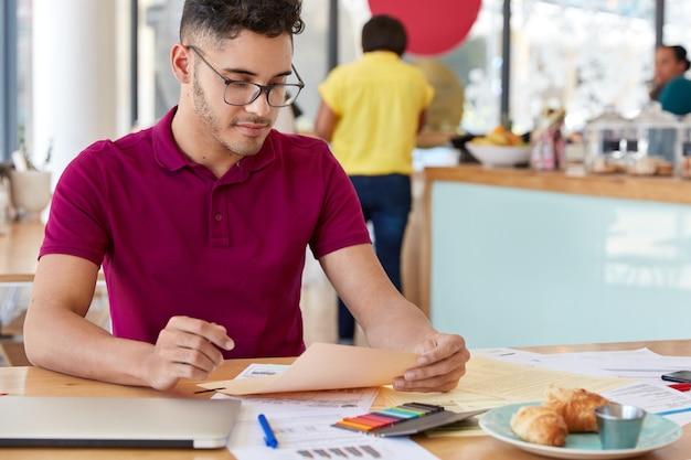 Bijgesneden afbeelding van mannelijke freelancer studies financieel verslag, maakt project, gekleed in vrijetijdskleding, zit op het bureaublad met kleurrijke stickers, croissants, draagt een casual outfit. papierwerk concept