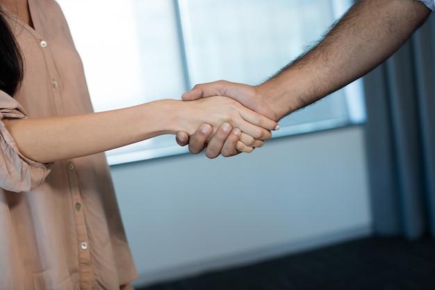 Bijgesneden afbeelding van mensen uit het bedrijfsleven handen schudden tijdens vergadering