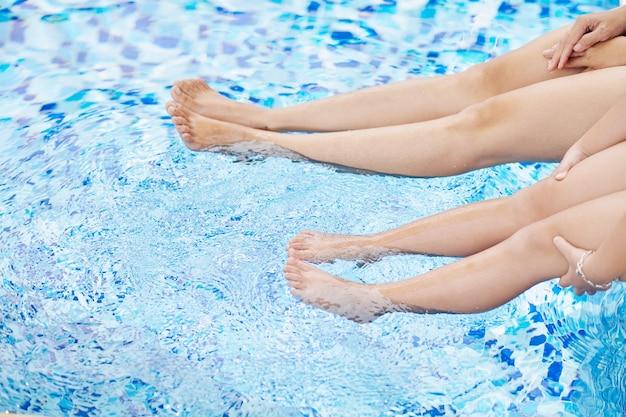 Bijgesneden afbeelding van moeder en dochter zittend op de rand van het zwembad en opspattend water