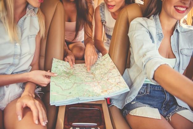 Bijgesneden afbeelding van mooie stijlvolle meisjes die de kaart bestuderen.