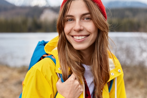 Bijgesneden afbeelding van mooie vrolijke europese vrouw heeft een brede tedere glimlach, lang steil haar, draagt een rode hoed