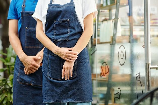 Bijgesneden afbeelding van obers of barista's in schorten die buiten een kleine coffeeshop of café staan