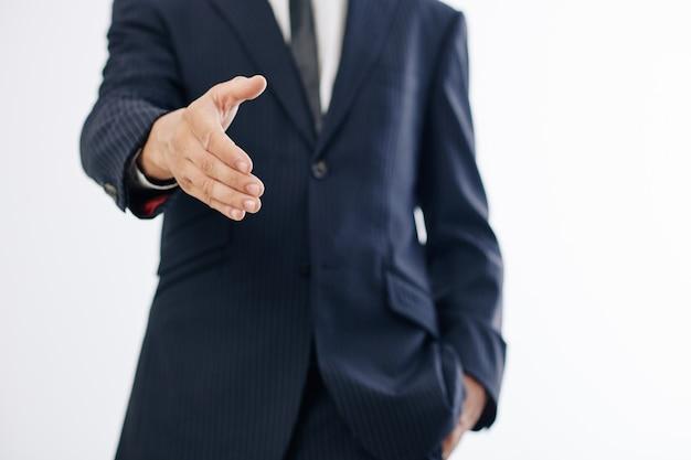 Bijgesneden afbeelding van ondernemer uitgestrekte hand voor handdruk bij het begroeten van collega
