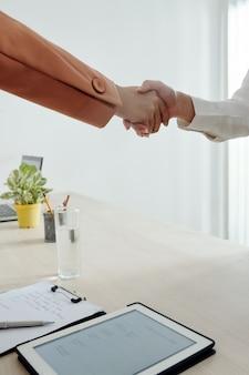 Bijgesneden afbeelding van personeelsmanager en sollicitant die handen schudden na succesvol sollicitatiegesprek