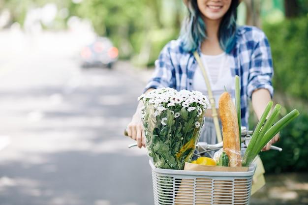 Bijgesneden afbeelding van positieve jonge vrouw zittend op de fiets met boeket en boodschappen vooraan mand