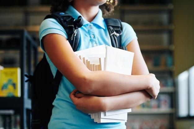 Bijgesneden afbeelding van schoolmeisje permanent in bibliotheek met set leerboeken