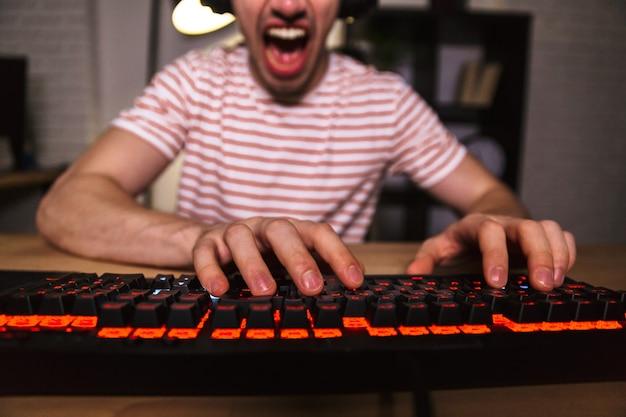 Bijgesneden afbeelding van schreeuwende gamer spelen van videogames op computer