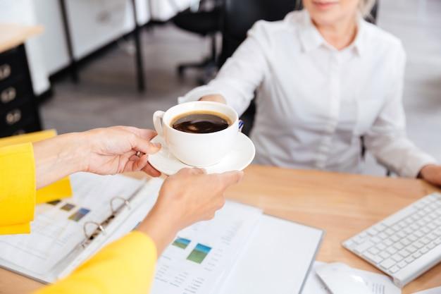 Bijgesneden afbeelding van secretaris kopje koffie brengen voor haar baas in kantoor