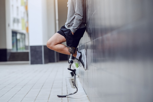 Bijgesneden afbeelding van sportman met kunstbeen staande tegen de muur en hand in hand in zakken.