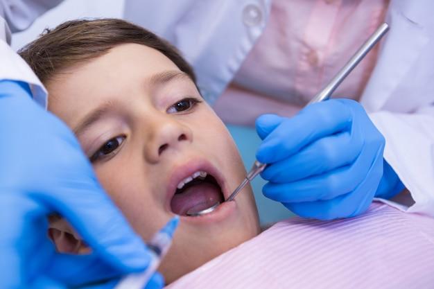 Bijgesneden afbeelding van tandarts die jongen onderzoekt