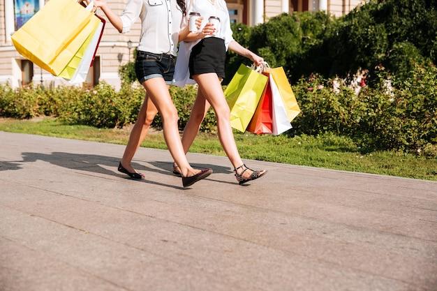 Bijgesneden afbeelding van twee vrouwen die langs straat lopen met boodschappentassen en koffiekopjes