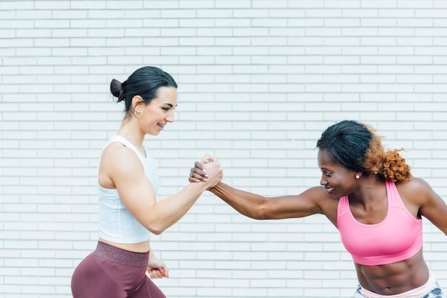 Bijgesneden afbeelding van twee vrouwen hand in hand. de hand links is van een blanke jonge vrouw. de foto aan de rechterkant is van een zwarte jonge vrouw.
