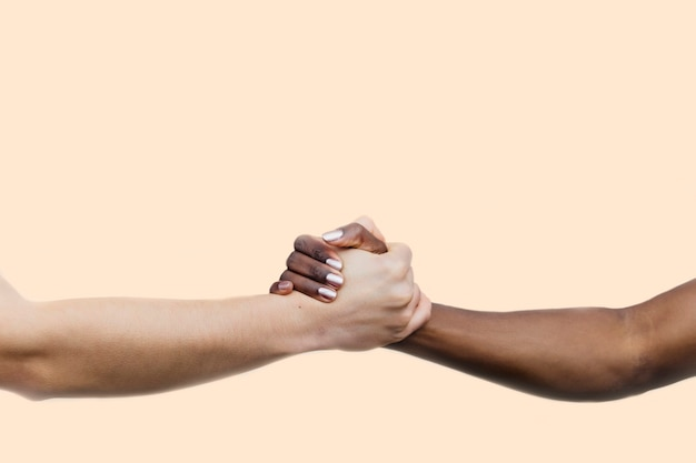 Bijgesneden afbeelding van twee vrouwen hand in hand. de linkerhand is van een blanke jonge vrouw met grijze nagels. de foto aan de rechterkant is van een zwarte jonge vrouw.