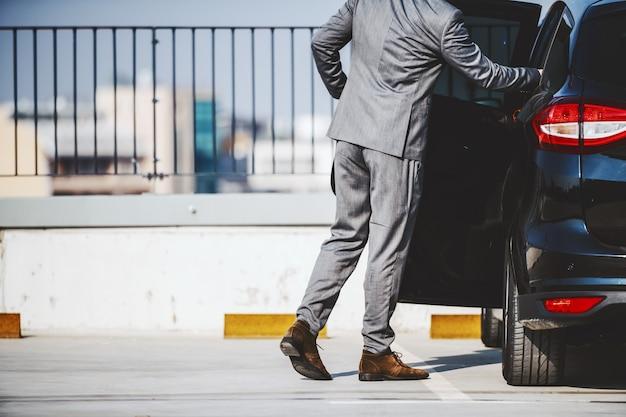 Bijgesneden afbeelding van verfijnde zakenman in pak die zijn moderne en dure auto betreedt.