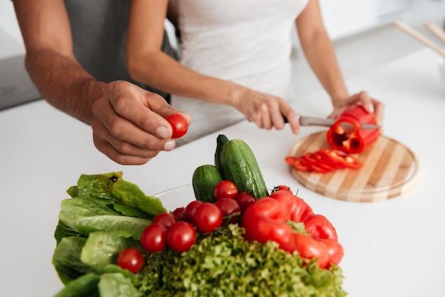 Bijgesneden afbeelding van verliefde paar in de keuken koken. de mens neemt de producten weg.
