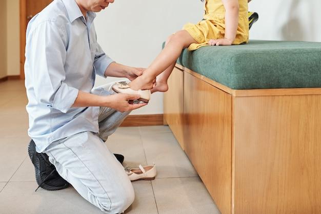 Bijgesneden afbeelding van volwassen aziatische man helpt dochtertje om schoenen te dragen