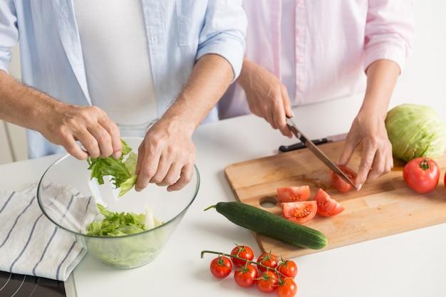Bijgesneden afbeelding van volwassen liefdevolle paar familie koken.