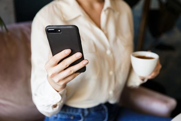 Bijgesneden afbeelding van vrij mooie jonge vrouw zitten in café binnenshuis werken koffie drinken met behulp van mobiele telefoon.