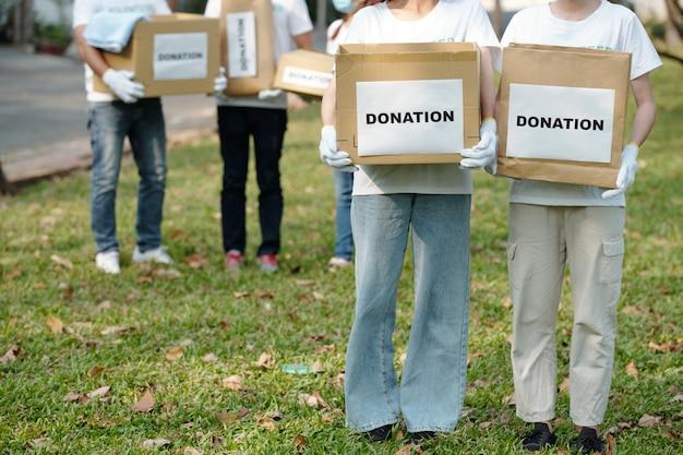 Bijgesneden afbeelding van vrijwilligers die dozen vasthouden met kleren die zijn gedoneerd voor opvang voor daklozen