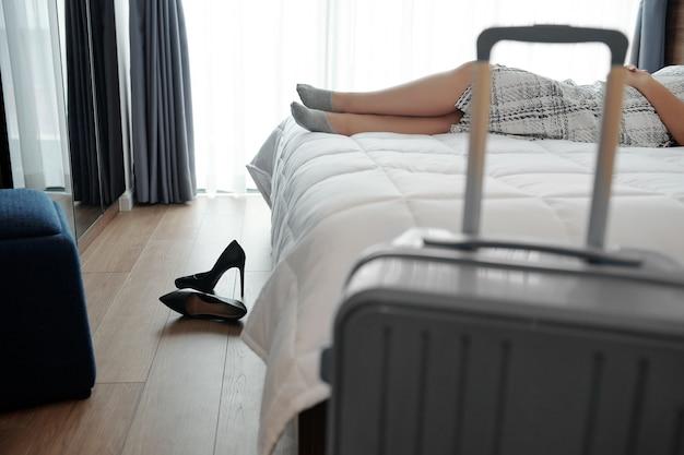 Bijgesneden afbeelding van vrouw die hakken uitdoet en op bed ontspant nadat ze naar de hotelkamer is gekomen