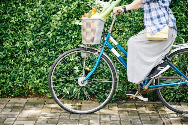 Bijgesneden afbeelding van vrouw fietsten met mandje met verse boodschappen