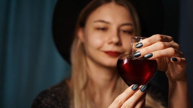 Bijgesneden afbeelding van vrouw met hartvormige glazen pot liefdesdrankje. mooie jonge vrouw in een heksenhoed. focus op potion of poison vial