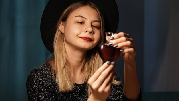Bijgesneden afbeelding van vrouw met hartvormige glazen pot liefdesdrankje. mooie jonge vrouw in een heksenhoed. glimlachende blondine die naar de fles kijkt
