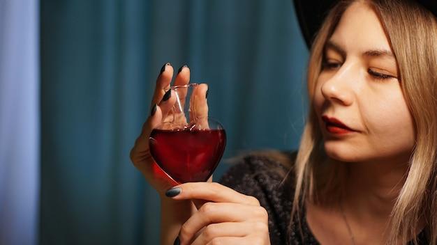 Bijgesneden afbeelding van vrouw met hartvormige glazen pot liefdesdrankje. mooie jonge vrouw in een heksenhoed