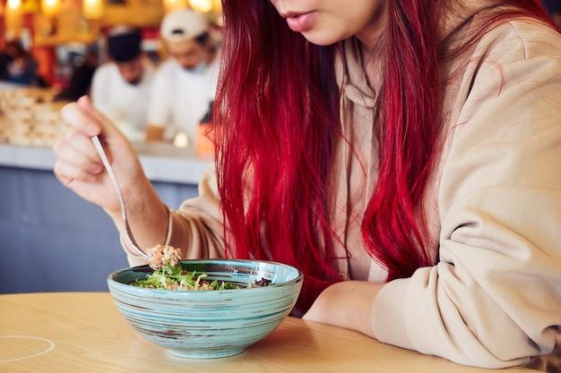 Bijgesneden afbeelding van vrouw met rood haar salade eten in een restaurant