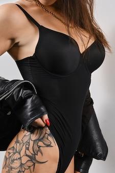 Bijgesneden afbeelding van vrouwelijk lichaam met tatoeage op heup
